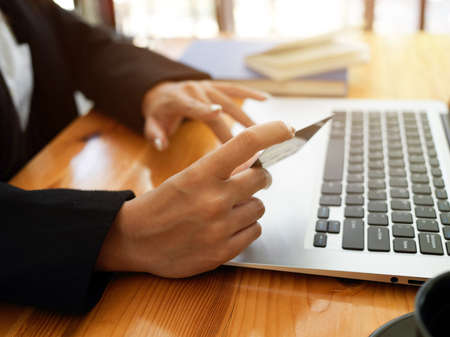 Side view of female holding credit card and typing on laptop keyboard to online paying