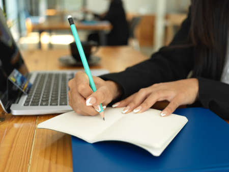 Close up view of businesswoman hand with pencil writing on notebook while working with laptop on the table