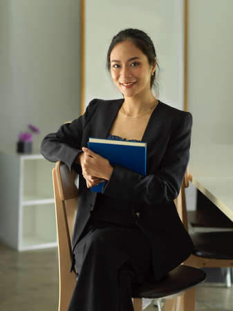 Portrait of female office worker holding textbook while sitting on the chair in library