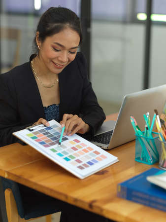 Portrait of female designer showing colour chart to her coworker while consulting on their project