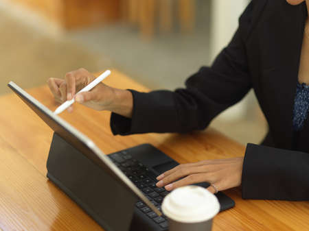 Cropped shot of female hand with stylus pen using digital tablet with keyboard on wooden table