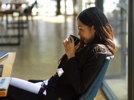 Close up view of businesswoman relaxing with coffee while sitting at workspace in co-working space