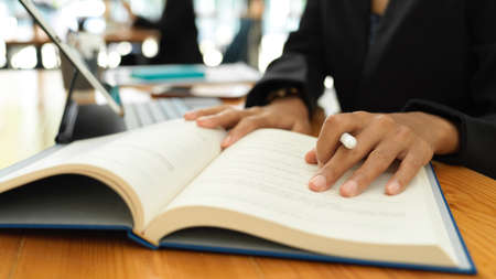 Close up view of female student reading textbook to prepare for her coming exam