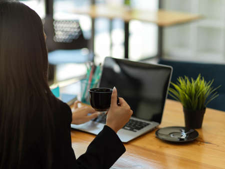 Cropped shot of businesswoman holding coffee cup and working with laptop on wooden table in cafe Stock Photo