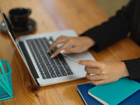 Cropped shot of female hand holding credit card and typing on laptop keyboard to online paying on workspace