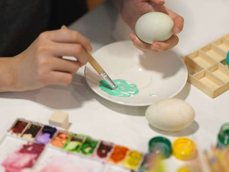 Cropped shot of hands painting egg with poster colour preparing for Easter festival Stock Photo