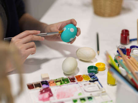 Cropped shot of female hand painting on egg preparing for Easter festival at home Stock Photo