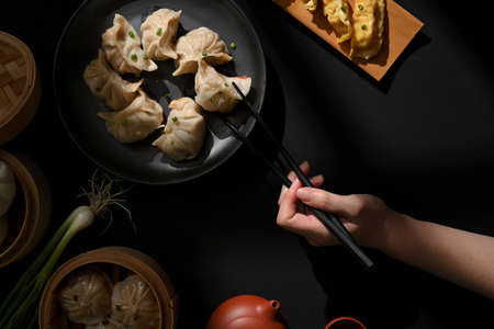 Top view of dinning table in Chinese restaurant, female hand with chopstick picking Dimsum dumplings
