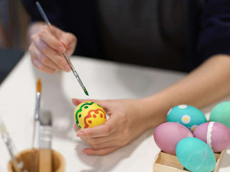 Close up view of female hand with paintbrush painting on egg preparing for Easter festival
