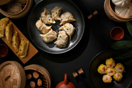 Top view of dinning table in Chinese restaurant with plate and bamboo steamer with dumplings and pork buns
