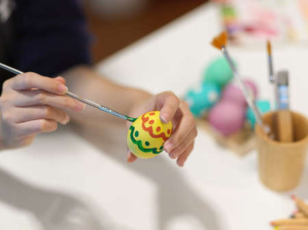 Close up view of female hand with paintbrush painting on egg, preparing for Easter festival