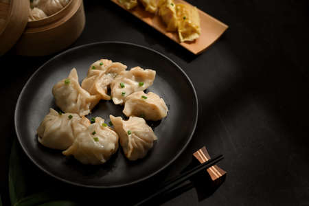 Top view of a plate of dumplings on dinning table with chopstick and copy space in Chinese restaurant Stock Photo