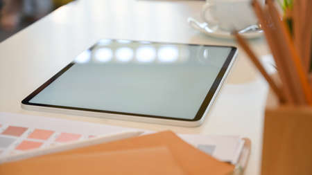 Side view of designer workspace with mock up digital tablet, stationery and designer supplies on the table Stock Photo