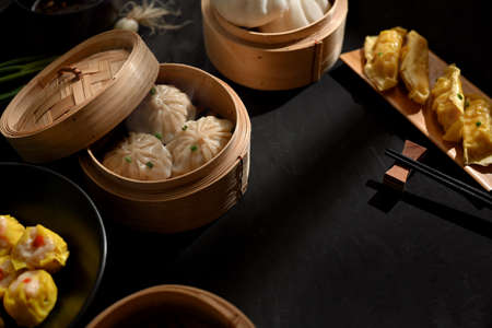 Top view of dinning table in Chinese restaurant with Dinsum dumplings on bamboo steamer and chopstick Stock Photo