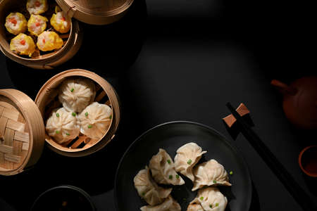 Top view of Dimsum on plate and bamboo steamer with dumplings on the table with copy space in Chinese restaurant