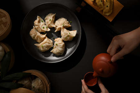 Top view of dinning table with Dimsum dumplings and female hand with tea pot in Chinese restaurant