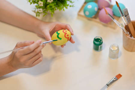 Cropped shot of female hand with paintbrush painting on egg, preparing for Easter festival