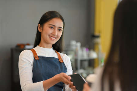 Portrait of young beautiful barista with apron holding over smartphone to help customer pay for purchase a coffee Imagens