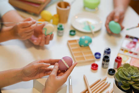 Cropped shot of people hands painting Easter egg, preparing for Easter Festival at home