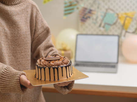 Cropped shot of female in sweater holding birthday cake in her hands with blurred background