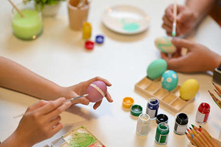 Cropped shot of two people painting Easter eggs with poster colour on craft table in living room