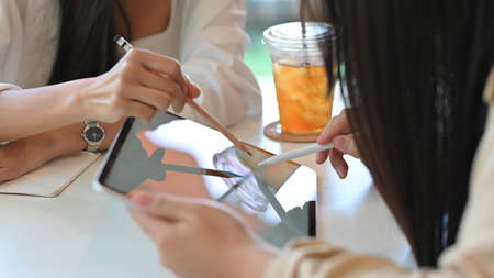 Cropped shot of young businesswomen working their project and using mock up digital tablet