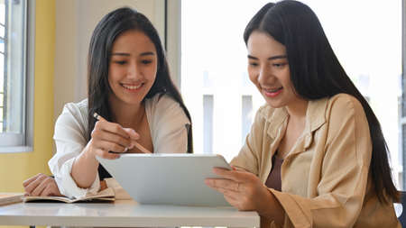 Portrait of two young pretty female students doing assignment with digital tablet in library