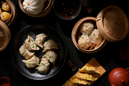 Top view of Dimsum on plate and bamboo steamer with dumplings and pork buns in Chinese restaurant Stock Photo
