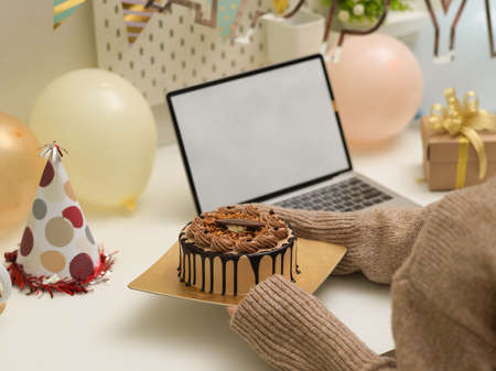 Cropped shot of female hands holding birthday cake on the table with birthday decorations and laptop Stock Photo