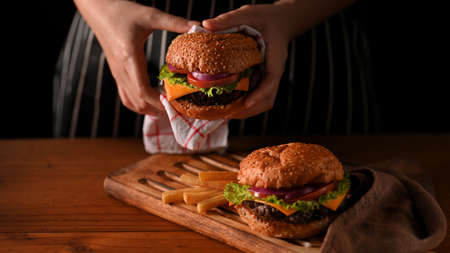 Close up view of young woman holding beef burgers with napkin in restaurant with black wall background