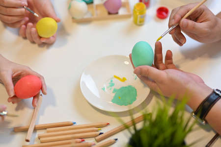 Top view of family preparing for Easter festival at home, painting on eggs