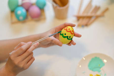 Close up view of female painting Easter egg, preparing for Easter Festival at home Imagens