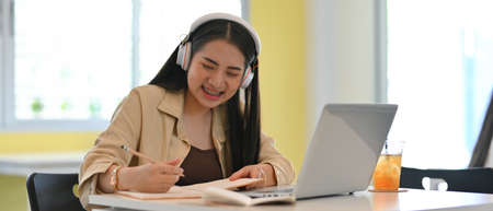 Portrait of young female student with headphone smiling while doing home working with stationery and laptop Stock Photo