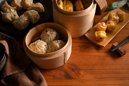 Top view of wooden kitchen table with Dimsum dumplings in bamboo steamers and copy space