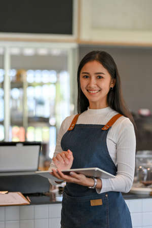 Portrait of female barista with apron smiling and working on digital tablet in front of counter bar Imagens