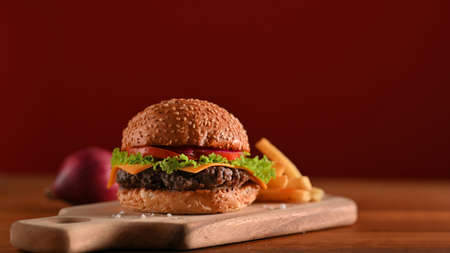 Fresh tasty beef burger and french fries served on wooden tray on the table in fast food shop with red wall background Stock Photo