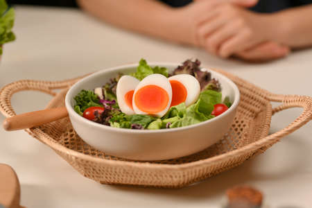Close up view of a plate of of salad with boiled eggs, lettuce and tomato on wicker tray in restaurant Stock Photo