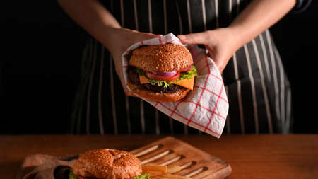 Young woman holding beef burgers with napkin in restaurant with black wall background