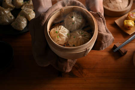Top view of hands holding bamboo steamer with dumplings to show to camera above kitchen table