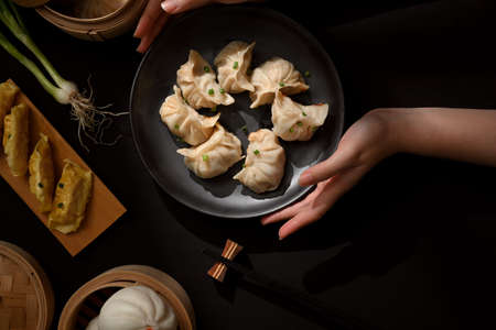Top view of female hands holding a plate of Dimsum dumplings to place on dining table
