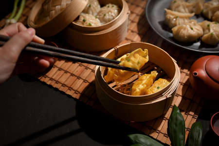 Cropped shot of female hand with chopstick picking Dimsum dumplings in bamboo steamer on dinning table