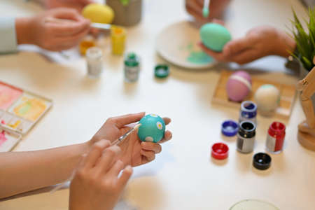 Cropped shot of young people hands painting on egg preparing for Easter festival at home Imagens