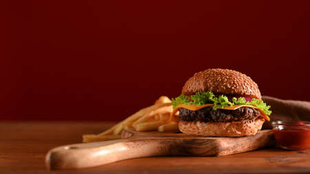 Delicious grilled beef burger and french fries served on wooden tray on the table in fast food shop with red wall background