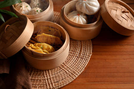 Cropped shot of bamboo steamers with dumplings and pork bun on wooded table in kitchen Imagens
