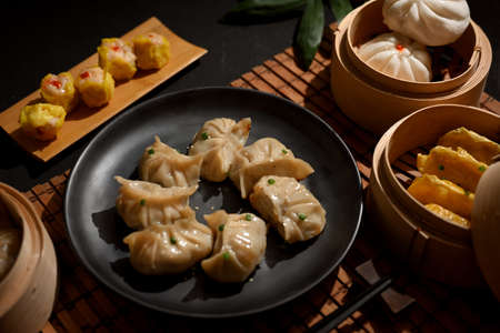 Cropped shot of a plate and bamboo steamer of Dimsum dumplings in Chinese restaurant Stock Photo