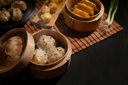 Cropped shot of bamboo steamers with dumplings and pork bun on dinning table in Chinese restaurant