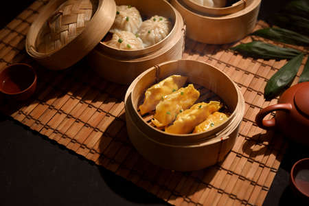 Cropped shot of Dimsum dumplings in bamboo steamer on dining table in Chinese restaurant