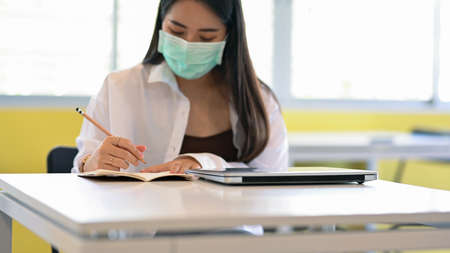Close up view of female student with surgical mask studying on the table in library