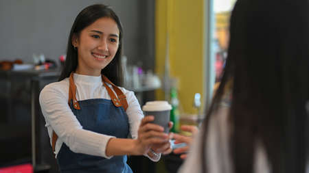 Portrait of young beautiful female giving a cup of beverage to her customer in coffee shop Imagens