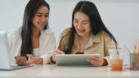 Close up view of two female students taking to each other while doing group assignment on digital tablet